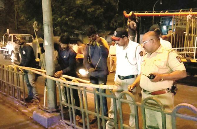 ٹریفک اہلکاروں کو گری ہوئی ریلنگ کو بانس سے باندھتے ہوئے دیکھا جا سکتا ہے۔ تصویر : انقلاب