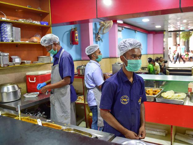 "<p style=""text-align: right;"">بنگلور میں ایک ریستوراں کے ملازمین ماسک پہن کر کھانے بناتے ہوئے دیکھے جاسکتے ہیں۔</p>"