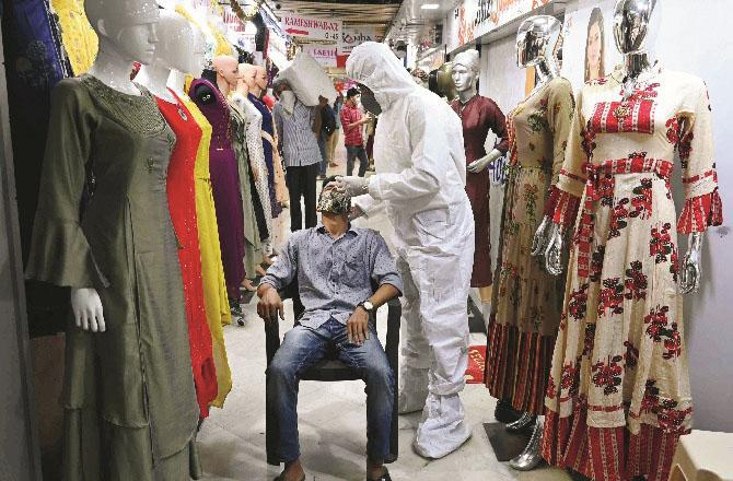 An employee of the clothing wholesale market is checking the health worker code.Pictrue: PTI