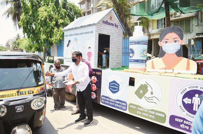 BMC officials distribute masks to the public to create awareness about prevention.Picture:PTI
