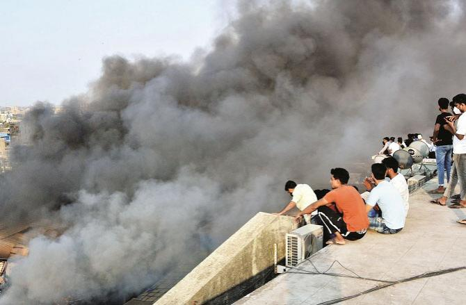 Smoke rising from the warehouse Some people are watching from the top of a building in the distance..Picture:Inquilab,Sameer Abidi