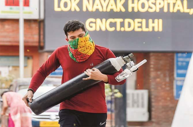 A man carries an oxygen cylinder for a relative undergoing treatment at the LNJP Hospital in Delhi.Picture:PTI