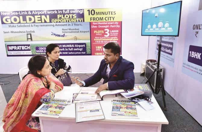 In the file photo of the Midday Hot Property Exhibition, two women take information about the new house .Picture:INN