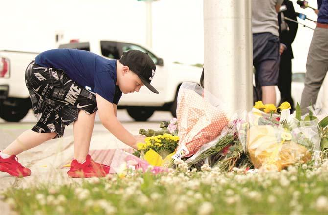 A child lays flowers in front of the memorial at the scene of the accident (Photo: Agency)