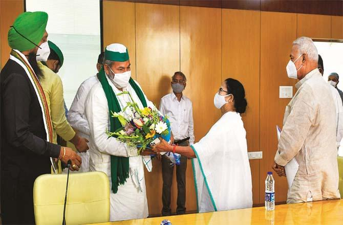 Chief Minister Mamata Banerjee taking a bouquet from farmer leader Rakesh Tikit during the meeting. Picture: PTI
