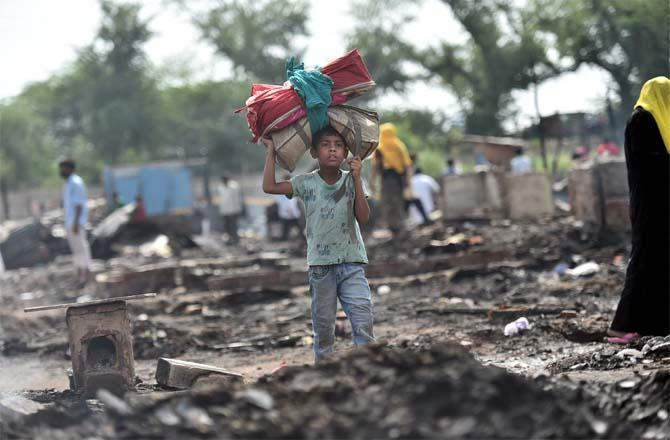 A boy stands between the ashes of Rohingya refugees. (Picture:PTI)