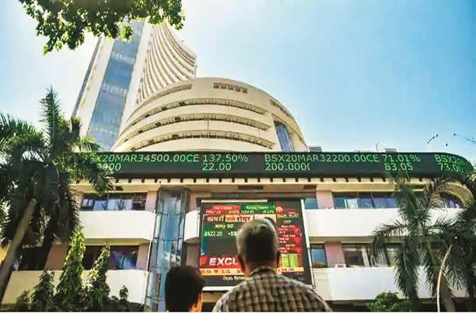 Two people look at the market on the screen outside the Bombay Stock Exchange. File photo